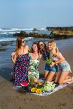 Group of smiling young women with various fruits spending time. On beach royalty free stock photos