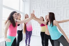 Young women wearing sportswear joining hands together. stock photography