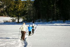 Snow shoers heading into the woods royalty free stock images