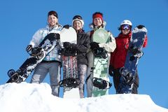 Group of snowboarders. Portrait of happy company of guys and girl with snowboards Royalty Free Stock Photo