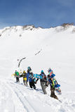 Group snowboarders climb the mountain for freeride. KAMCHATKA PENINSULA, RUSSIAN FEDERATION - MARCH 9, 2014: Group of snowboarders climbing the mountain for Stock Photos