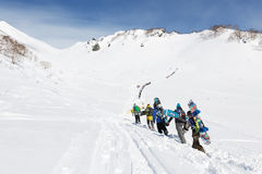 Group snowboarders climbing the steep mountain for freeride. KAMCHATKA PENINSULA, RUSSIA - MARCH 9, 2014: Sportsmens - snowboarders climbing the steep mountain Royalty Free Stock Photos