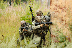 Group of soldiers attacking from behind cover Royalty Free Stock Photos