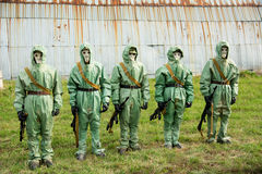 A group of soldiers with guns in their masks and protective clot Stock Photos