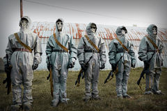 A group of soldiers with guns in their masks and protective clot. Hing Royalty Free Stock Photography