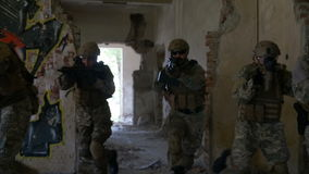 Group of soldiers moving fast through the ruined building in search and rescue operation. Group of soldiers moving fast through ruined building in search and stock video