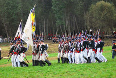 A group of soldiers-reenactors march with a flag. Stock Photos