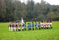 A group of soldiers-reenactors march with a flag. Royalty Free Stock Photos