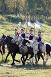 Group of soldiers-reenactors ride horses, two men carry flags. Stock Photos