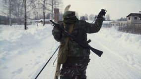 Group of soldiers run on skis in the woods with weapons. Clip. Soldiers with AK-47 rifles and grenade launchers running royalty free stock photography