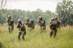 Group of soldiers running across the field and shoot Royalty Free Stock Photo