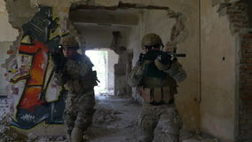 Group of soldiers spreading inside the ruins of building searching for fallen comrades and shooting targets stock video