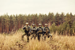 Group of soldiers standing with arms and looking at the camera Royalty Free Stock Images