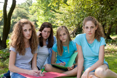 Group of sombre young teenagers. Group of sombre young female teenagers sitting together on a rug outdoors staring at the camera with serious expressions Royalty Free Stock Images