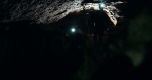 Group of speleologists with flashlights walks in a dark cave