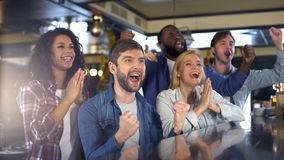 Group of sport fans watching game in bar, rejoicing victory of favorite team royalty free stock image