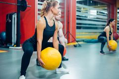 Cross fit woman with ball in gym. Group of sport people. Camera focus on the woman. Active athletic women doing squats workout with ball in gym Stock Photo