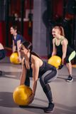 Cross fit woman with ball in gym. Group of sport people. Camera focus on the woman. Active athletic women doing squats workout with ball in gym Stock Photos