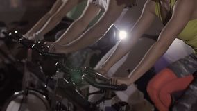 Group of sport people at fitness club exercising on stationary bikes. Camera moves down stock video footage