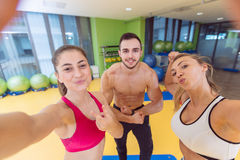 Group of sportive people in a gym taking selfie. Happy sporty friends in a weight room while training - Concepts about lifestyle and sport in a fitness club Stock Photos