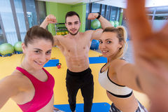 Group of sportive people in a gym taking selfie. Happy sporty friends in a weight room while training - Concepts about lifestyle and sport in a fitness club Royalty Free Stock Images