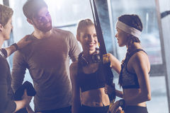 Group of sportive people near trx equipment in gym. Portrait of group of sportive people near trx equipment in gym Royalty Free Stock Photos