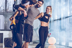 Group of sportive people near trx equipment in gym. Side view of group of sportive people near trx equipment in gym Stock Images