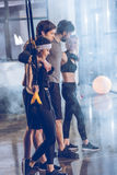 Group of sportive people near trx equipment in gym. Side view of group of sportive people near trx equipment in gym Royalty Free Stock Images