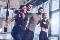 Group of sportive people near trx equipment in gym. Side view of group of sportive people near trx equipment in gym Royalty Free Stock Image