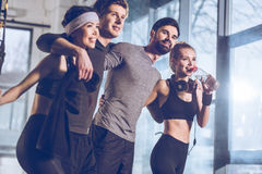 Group of sportive people near trx equipment in gym Royalty Free Stock Image