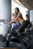 Two beautiful girls with their coach working out of cycling in modern fitness club. Group of sportive people working out of cycling in modern fitness club stock photo
