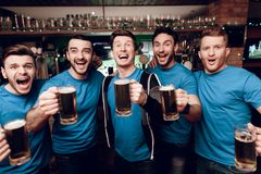 Group of sports fans drinking beer celebrating and cheering at sports bar. They are supporting blue team stock photos