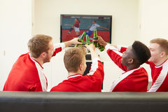 Group Of Sports Fans Watching Game On TV At Home. Holding Bottle Of Beer Making A Cheer Stock Image