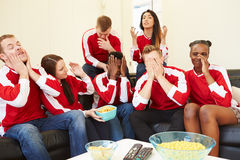 Group Of Sports Fans Watching Game On TV At Home. Looking Disappointed Royalty Free Stock Photo