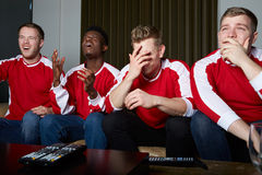 Group Of Sports Fans Watching Game On TV At Home. Looking Disappointed Stock Photography