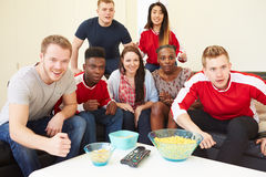 Group Of Sports Fans Watching Game On TV At Home. Sitting On Sofa Stock Photos