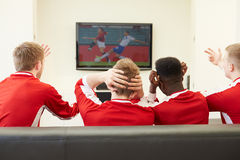 Group Of Sports Fans Watching Game On TV At Home. Group Of Unhappy Sports Fans Watching Game On TV At Home Wearing Football Shirts Stock Photos