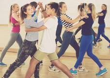 Group of sports teen dancing tango in dance studio Royalty Free Stock Image