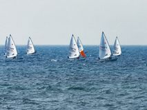 A group of sportsmans on small sailing yachts trains on the Mediterranean Sea near the coast of Nahariyya in Israel. Nahariyya, Israel - Februar 10, 2018 : A Stock Photos