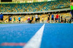 Group of sportsmen do the exersises on the stadium. squat and stretch. stock photos
