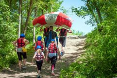 A group of athletes in sports equipment carries rubber inflatable boats to the place where the alloy begins. stock image