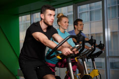 Group sportsmens on stationary bike Stock Images