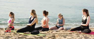 Group of sporty girls practicing various yoga positions during t stock photos