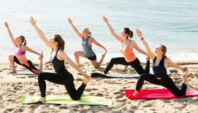 Group of sporty girls practicing various yoga positions during t. Group of positive sporty girls practicing various yoga positions during training on beach royalty free stock photo