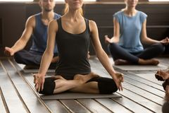 Group of sporty people in Easy Seat pose, close up. Photo of group of young sporty people practicing yoga lesson, sitting in Sukhasana exercise, Easy Seat pose stock photography