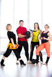 Group of sporty people holding dumbbells in gym Stock Images
