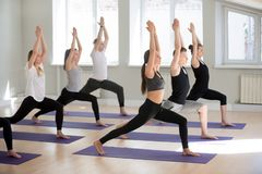 Group of sporty people practicing yoga, doing Warrior one pose royalty free stock photography