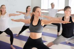 Group of sporty people practicing yoga, doing Warrior 2 pose royalty free stock photo