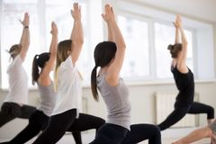 Group of sporty people practicing yoga, doing Warrior 1 pose stock photo