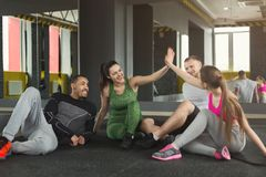 Group of sporty people sitting on floor at gym. Group of young sporty smiling people sitting on floor, talking after successful workout, friends having rest Royalty Free Stock Photo